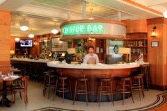 Молодой бармен стоя за приветствующими светами, грандиозный ресторан острова, Новый Орлеан, 2016 Стоковая Фотография RF