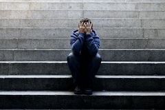 Молодой бездомный человек потерял работу сидя в депрессии на земных лестницах бетона улицы Стоковое фото RF