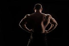 Молодой без рубашки спортсмен изгибая задние мышцы стоковая фотография