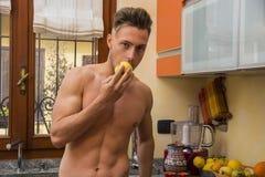 Молодой без рубашки человек есть яблоко в кухне Стоковая Фотография