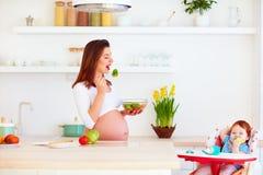 Молодой беременный младенец матери и младенца в высоком стульчике имея обед на кухне дома Стоковые Изображения RF