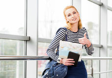 Молодой белокурый большой палец руки положения и выставок женщины в камеру, удерживание таблетка карточки и рюкзак Стоковое фото RF