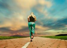 Молодой белокурый вечер девушки jogging с большим cloudscape Стоковая Фотография RF