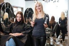 Молодой белокурый женский парикмахер держа ножницы и гребень стоковые фотографии rf