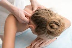 Молодой белокурый наслаждаясь массаж шеи в салоне стоковая фотография
