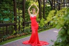 Молодой белокурый портрет женщины нося элегантное красное платье в деревянных руках в волосах Стоковое Фото