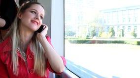 Молодой белокурый трамвай катания женщины, говоря на черни, телефон, клетка сток-видео