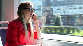 Молодой белокурый трамвай катания женщины, говоря на черни, телефон, клетка видеоматериал