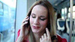 Молодой белокурый трамвай катания женщины, говоря на черни, телефон, клетка, держа стекла видеоматериал