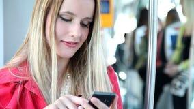 Молодой белокурый трамвай катания женщины, печатая на черни, телефон, клетка видеоматериал