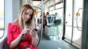 Молодой белокурый трамвай катания женщины, печатая на черни, телефон, клетка, держа стекла видеоматериал