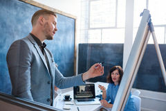 Молодой бизнесмен давая коллегам представление в офисе Стоковое Фото