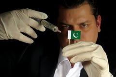 Молодой бизнесмен дает финансовую впрыску к флагу пакистанца стоковая фотография