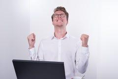Молодой бизнесмен веселя его успех пока работающ на компьтер-книжке Стоковые Изображения RF