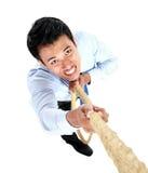 Молодой бизнесмен взбираясь вверх путем использование веревочки стоковое фото