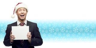 Молодой бизнесмен в удерживании шляпы santa подписывает сверх backgro зимы Стоковые Изображения