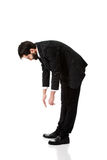 Молодой бизнесмен гнуть вниз Стоковое фото RF