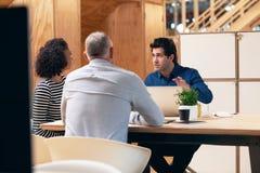 Молодой бизнесмен говоря над компьтер-книжкой с коллегами офиса Стоковая Фотография