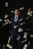 Молодой бизнесмен держа банкноты бейсбольной биты и доллара падая на черноту Стоковое Изображение