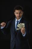 Молодой бизнесмен держа банкноты бейсбольной биты и доллара смотря камеру Стоковая Фотография