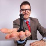 Молодой бизнесмен держит черного короля шахмат в руке Стоковое Фото