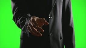 Молодой бизнесмен делая жесты рукой в виртуальной экономической обстановке на зеленом экране