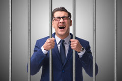Молодой бизнесмен за барами в тюрьме Стоковые Фото