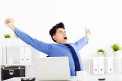 Молодой бизнесмен зевая на работе в офисе стоковые изображения rf