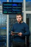 Молодой бизнесмен инженера с таблеткой в roo сетевого сервера Стоковые Фотографии RF