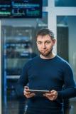Молодой бизнесмен инженера с таблеткой в roo сетевого сервера Стоковое фото RF