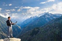 Молодой бизнесмен используя его компьтер-книжку на верхней части горы Стоковые Изображения RF