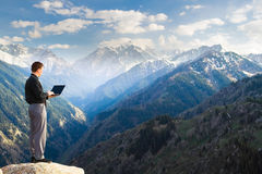 Молодой бизнесмен используя его компьтер-книжку на верхней части горы Стоковое Изображение