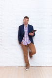 Молодой бизнесмен используя стойку связи системы планшета социальную над стеной Стоковое Фото