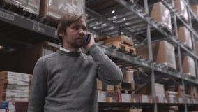 Молодой бизнесмен используя таблетку и мобильный телефон цифров в складе сток-видео