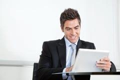 Молодой бизнесмен используя таблетку цифров в офисе Стоковое фото RF