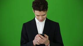 Молодой бизнесмен используя smartphone на предпосылке ключа chroma акции видеоматериалы