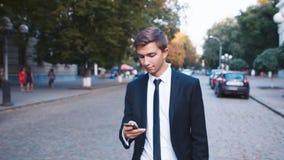 Молодой бизнесмен идя вниз с улицы, говоря на клетке акции видеоматериалы