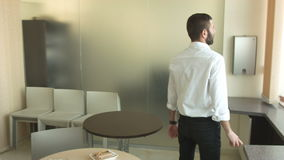 Молодой бизнесмен идя вокруг кухни в офисе видеоматериал
