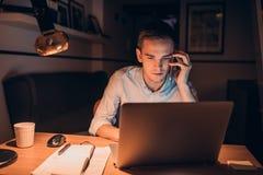 Молодой бизнесмен крепко на работе поздно вечером Стоковые Изображения