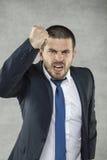 Молодой бизнесмен крича и угрожает кулака стоковое изображение rf