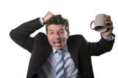 Молодой бизнесмен наркомана в костюме и связь держа пустую чашку кофе тревоженый Стоковые Фотографии RF