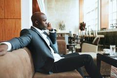Молодой бизнесмен на лобби гостиницы звоня телефонный звонок Стоковые Фотографии RF