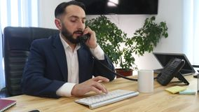 Молодой бизнесмен на телефоне в офисе видеоматериал