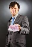 Молодой бизнесмен показывая банкноты и подмигивать евро Стоковые Фото