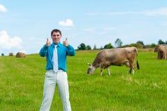 Молодой бизнесмен показывая большие пальцы руки вверх на заднем плане зеленой травы и коров Стоковая Фотография