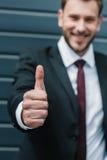 Молодой бизнесмен показывая большой палец руки вверх и усмехаясь на камере Стоковое Фото