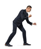 Молодой бизнесмен представляя как он вытягивая веревочка над его плечом изолированным на белой предпосылке стоковые фото