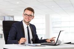 Молодой бизнесмен представляя перед компьтер-книжкой стоковое изображение rf