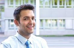 Молодой бизнесмен при голубая связь смотря камеру Стоковые Изображения RF