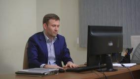 Молодой бизнесмен работая в офисе, сидящ на столе, смотря экран компьютера акции видеоматериалы